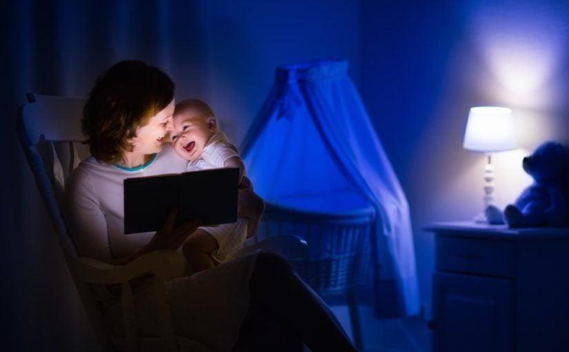 Mor der læser godnathistorie for sin baby, med en natlampe i baggrunden